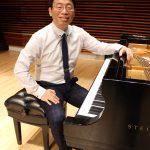 Chih-Long Hu portrait sitting at piano